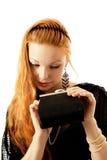 La fille regarde dans un sac à main Photo stock