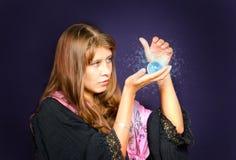 La fille regarde dans une sphère en cristal Photographie stock libre de droits