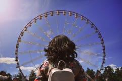 La fille regarde la grande roue image stock