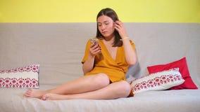 La fille regarde l'écran de téléphone, utilise un smartphone banque de vidéos