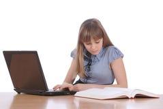 La fille regarde l'ordinateur portable de configurations tacheté par livre images stock
