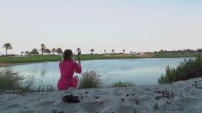 La fille regarde le jeu sur le terrain de golf le crépuscule, fait la photo de selfie Tours de boguet par le champ La femme repos banque de vidéos