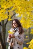 La fille regarde les feuilles jaunes image stock