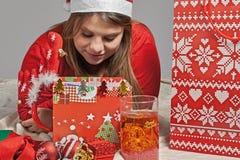 La fille regarde son cadeau Photographie stock libre de droits