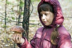 La fille regarde sur le champignon blanc dans sa main Image stock