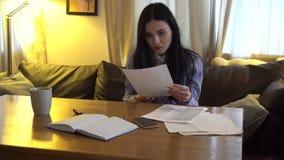 La fille regarde sur le papier dans le bureau et se demande banque de vidéos
