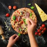 La fille remet la fabrication, decopating, préparant la pizza avec des feuilles de basilic sur le fond foncé Vue supérieure, l'es Photos stock