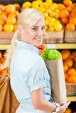 La fille remet le paquet avec les légumes frais Photos libres de droits