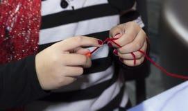 La fille remet le tricotage avec le crochet de crochet et le fil rouge Photographie stock libre de droits