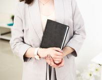 La fille remet un livre dans des ses mains, habill?es dans la veste grise Elle a une montre-bracelet sur sa main Fond blanc photo libre de droits