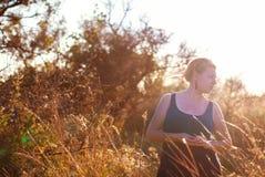 La fille rencontre un coucher du soleil d'or Photographie stock libre de droits