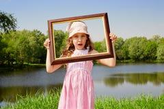 La fille reste sur le côté de l'étang et retient le cadre de tableau photos libres de droits