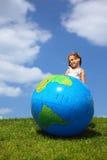 La fille reste et regarde de côté à côté d'un globe Images libres de droits