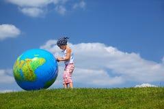 La fille reste sur l'herbe et les pièces avec le globe Image libre de droits