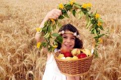 La fille retient le panier du fruit dans le domaine du blé Photo stock