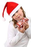 La fille retient peu se présente dans le chapeau de Santa d'isolement Photographie stock
