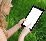 La fille retient une tablette sur un fond d'herbe verte Photographie stock