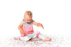 La fille riante d'enfant en bas âge regarde le plancher sur le papier tombé Co Images stock