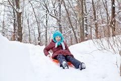 La fille roule sur une glissière sur le traîneau pendant l'hiver Photo stock