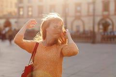 La fille rousse dans une jupe marche et tourne sa tête à la ville photographie stock