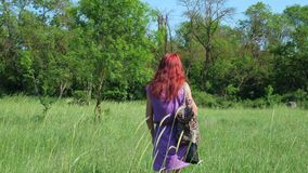 La fille rousse dans une robe lilas, avec un sac à dos et un sac des herbes médicinales marche par un pré herbeux banque de vidéos