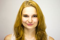 La fille rousse dans une veste blanche sourit confus à l'appareil-photo photographie stock libre de droits