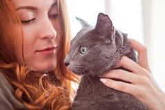 La fille rousse gaie joue avec son chat bleu Photos libres de droits