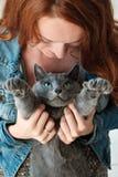 La fille rousse gaie joue avec son chat bleu Images stock