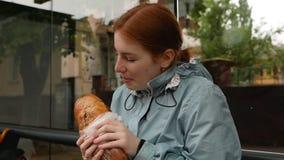 La fille rousse heureuse ont plaisir à manger la baguette banque de vidéos