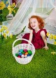 La fille rousse rit près d'un panier de Pâques Photos stock
