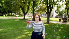 La fille rousse souffle des bulles de savon dans le mouvement lent de parc clips vidéos