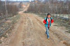 La fille russe de village va à l'école sur un chemin de terre Photographie stock libre de droits
