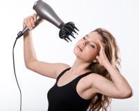 La fille sèche de longs cheveux avec le hairdryer photographie stock libre de droits