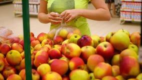 La fille sélectionne des pommes dans le supermarché banque de vidéos