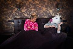 La fille sérieuse dans le pyjama s'assied sur le lit avec l'ami image stock