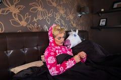 La fille sérieuse dans le pyjama se trouve sur le lit avec l'ami étrange Photos libres de droits
