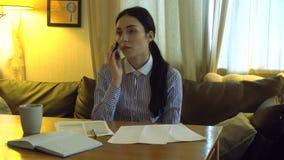 La fille sérieuse s'assied dans le bureau et l'entretien au téléphone banque de vidéos
