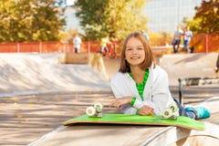 La fille s'étend près de la planche à roulettes verte avec des roues  Image libre de droits