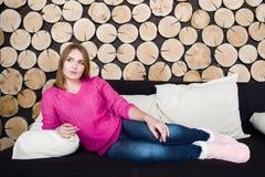 La fille s'étend sur le sofa sur le fond en bois Photographie stock