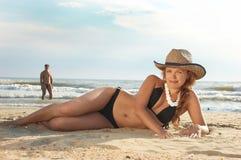 La fille s'étend sur une plage dans un chapeau Images libres de droits