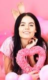 La fille s'étendent près des ballons, jouet de coeur de prises, fond rose Brune sur le visage de sourire rêvant de l'amour et de  Photographie stock libre de droits