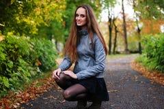 La fille s'accroupit en bois d'automne dans les faisceaux brillants du soleil Photo libre de droits