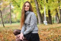 La fille s'accroupit en bois d'automne dans les faisceaux brillants du soleil Photo stock