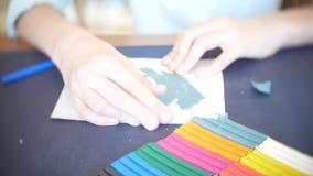 La fille s'asseyant à la table, tire les figures différentes de la pâte à modeler de modèle de couleur Développement d'art modela clips vidéos