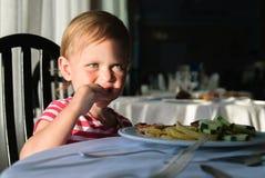La fille s'asseyant à une table dans un restaurant et mange Photo stock