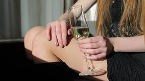 La fille s'asseyant dans sa main tient un de verre, en gros plan banque de vidéos