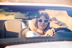 La fille s'asseyant derrière la roue d'un convertible blanc image stock