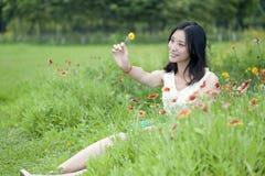 La fille s'asseyant en mes fleurs de prise de main sourient Images stock