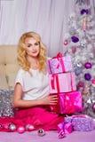 La fille s'asseyant sur le divan et met des cadeaux de Noël Photos libres de droits