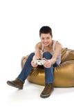 La fille s'asseyant sur un sac joue le jeu vidéo Photographie stock libre de droits
